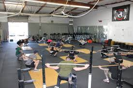 Un coach CrossFit entrain d'enseigner le Backsquat